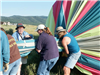 People Holding Part of a Deflated Hot Air Balloon